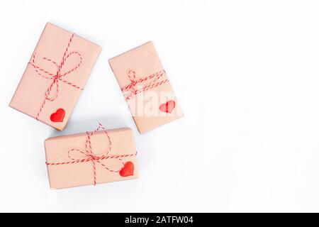 Gift boxes wrapped in craft paper and decorated with red ribbon and wooden hearts on white background. Valentines day, wedding or other holiday decorations background - Stock Photo