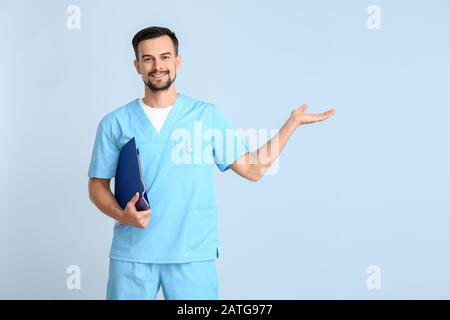Portrait of male doctor showing something on color background - Stock Photo