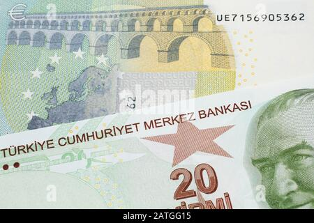 A close up image of a red, yellow and green twenty Turkish lira bank note with a German five euro bill in macro - Stock Photo