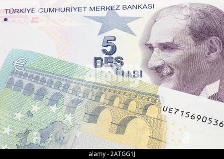 A close up image of a purple five Turkish lira bank note with a German five euro bill in macro - Stock Photo
