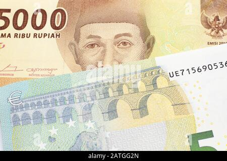 An orange five thousand Indonesian rupiah bank note with a five Euro note - Stock Photo