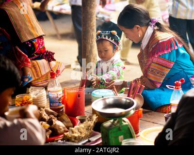 A Flower H'mong (Flower Hmong) woman and child in traditional dress share a moment over a meal at the Bac Ha Market in Bac Ha, Lao Cai, Vietnam. - Stock Photo