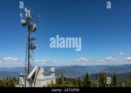 Telecommunications tower located high up on the hilltop of Kootenay valley mountains, in Creston, British Columbia, Canada - Stock Photo