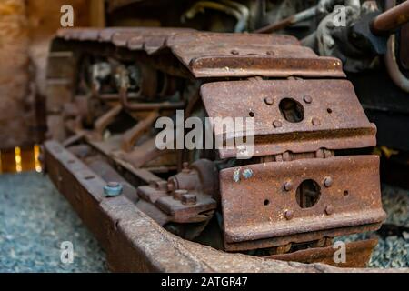 An old vintage agricultural crawler tractor in the museum, Kootenays, British Columbia, Canada. Close-up view agricultural technique - Stock Photo