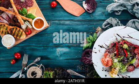 Assortment of healthy food. Cold and hot snacks. On a wooden background. Top view. Copy space. - Stock Photo