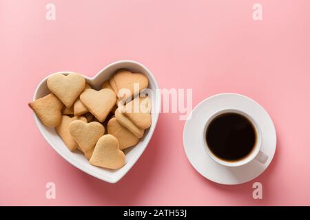 Cup of coffee and homemade cookies in plate shaped of heart on pink. Valentine card. Flat lay. View from above. Space for text. - Stock Photo