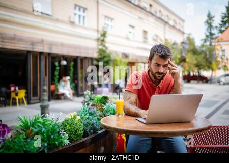 Stressed, tired young man sitting in front of laptop in the cafe - Stock Photo