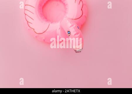 Summer beach composition. Simply minimal design with Inflatable flamingo isolated on pastel pink background. Pool float party, trendy celebrity fashion concept. Flat lay top view copy space - Stock Photo