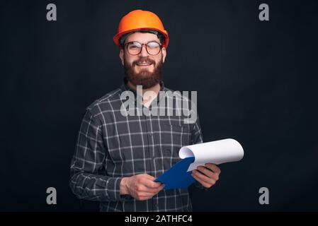 Handsome bearded engineer,constructor or architect is smiling at the camera, holding a paper board on black background. - Stock Photo