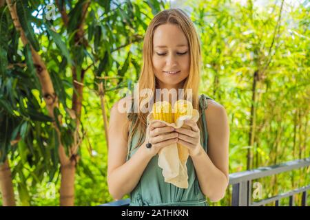 Corn in a reusable bag in the hands of a young woman. Zero waste concept - Stock Photo