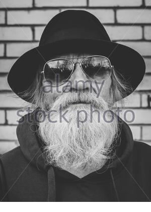 Black and white portrait of an elderly gray-haired man with a beard in a sunglasses and black hat looking at camera. - Stock Photo