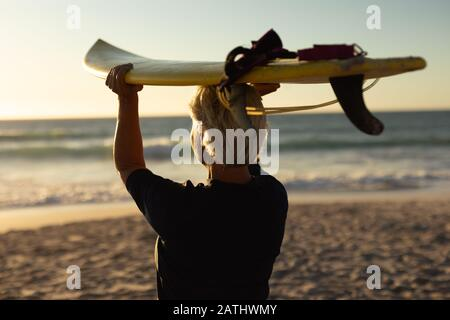 Old woman with a surfboard at the beach - Stock Photo