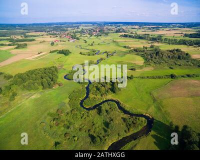 Meander of Goldapa river flowing in the vicinity of Banie Mazurskie, Mazury, Poland - Stock Photo