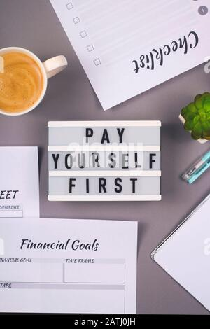 Pay yourself first. It is written on a decorative panel on the gray workplace of a freelancer who counts finances and makes savings.