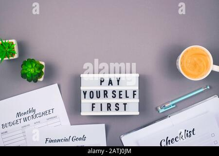 Pay yourself first. It is written on a decorative panel on the gray workplace of a freelancer who counts finances and makes savings. Background with copy space.