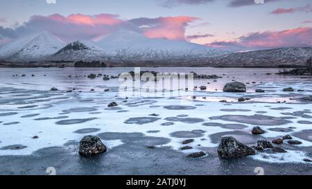Sunrise over a frozen Lochan na h-achlaise on Rannoch Moor near the entrance to Glencoe in the Scottish Highlands