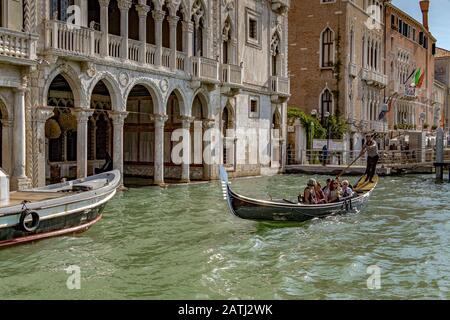 A gondolier taking tourists for a gondola ride past the Ca' d'Oro a Gothic Palace ,along The Grand Canal ,Venice ,Italy - Stock Photo