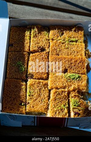 Take Away Turkish Dessert Kadayif with Pistachio Powder in Plastic Box / Package. Traditional Food. - Stock Photo