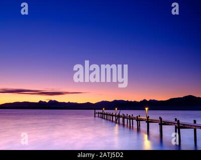Footbridge at Chiemsee at dawn, behind the Chiemgau Alps, Chiemgau, Upper Bavaria, Bavaria, Germany - Stock Photo