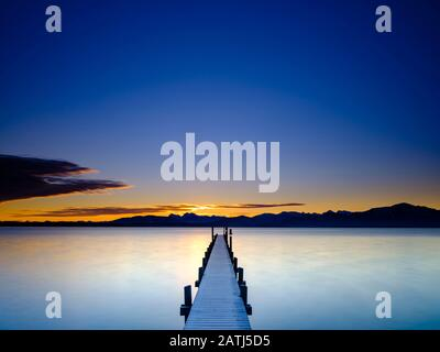 Footbridge at Chiemsee at sunrise, behind the Chiemgau Alps, Chiemgau, Upper Bavaria, Bavaria, Germany - Stock Photo
