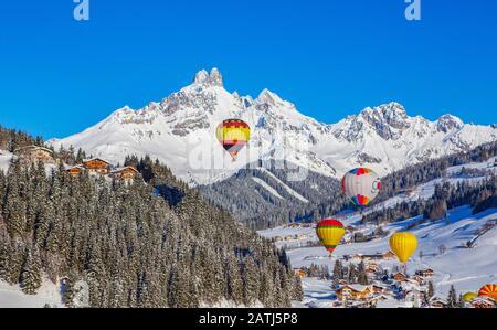 Hot air balloons, Filzmoos in winter with mountain peak Bischofsmuetze, Pongau, Province of Salzburg, Austria - Stock Photo