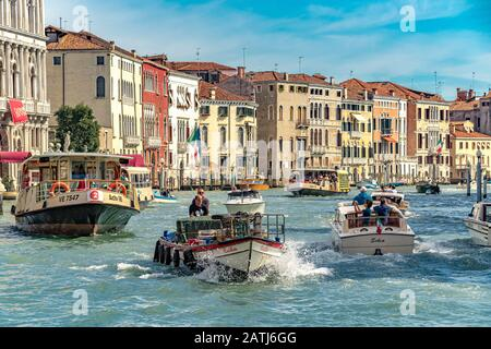 Busy water traffic on The Grand Canal including a Route No 2 Vaporetto or water bus ,water taxis and a boat carrying supplies ,Venice,Italy - Stock Photo