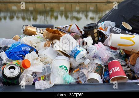 PARIS - NOVEMBER 8, 2019: Full garbage basket with colorful rubbish in Paris - Stock Photo