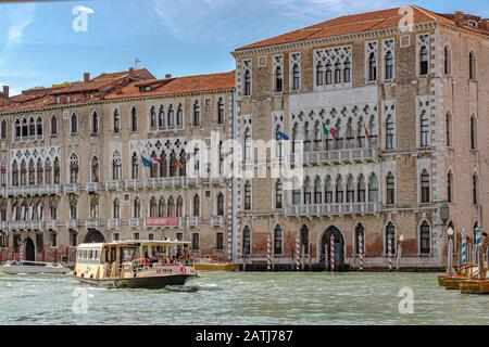 A route No 2 Vaporetto or water bus passing  Ca' Foscari and Palazzo Giustinian on The Grand Canal in Venice ,Italy - Stock Photo