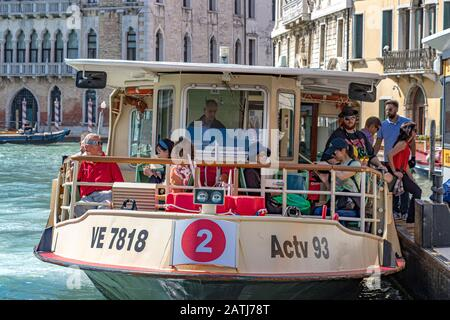 Passengers disembarking a No 2 Vaporetto or water bus at S Toma Vaporetto station on The Grand Canal ,Venice,Italy - Stock Photo