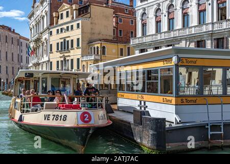 Passengers aboard a route no 2 vaporetto at S Toma vaporetto or water bus stop on The Grand Canal ,Venice ,Italy - Stock Photo