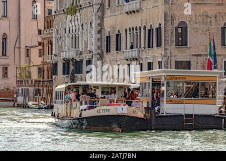 Passengers on a  route No 1 Vaporetto or water bus at Ca' Rezzonico Vaporetto stop on The Grand Canal ,Venice,Italy - Stock Photo
