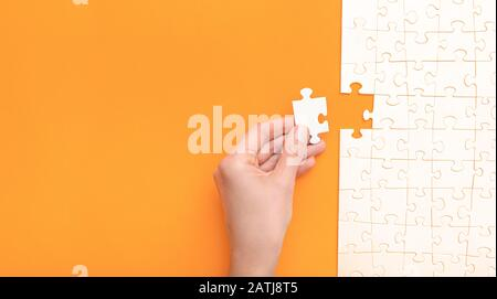 Hand put the last piece of jigsaw puzzle. Complete the mission. Business concept. - Stock Photo