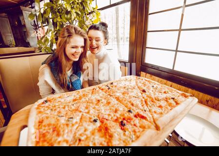 Girls in a pizzeria with a huge sliced pizza. Big pizza on the table. Girlfriends in a cafe - Stock Photo