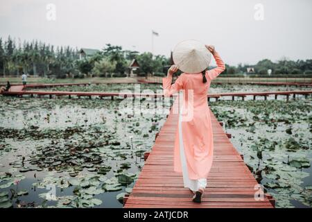 The backside of young tourist woman wearing Ao Dai Vietnam traditional dress