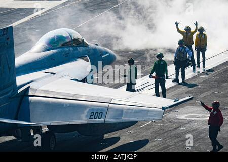 A U.S. Navy Sailors carry out pre-flight checks on a FA-18F Super Hornet fighter aircraft attached to Strike Fighter Squadron 211, before it takes off from the flight deck of the aircraft carrier USS Harry S. Truman following a routine patrol January 9, 2020 in the Arabian Sea. - Stock Photo