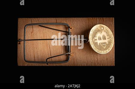 Bitcoin coin in a mousetrap isolate on a black background. Stock photo bitcoin news.