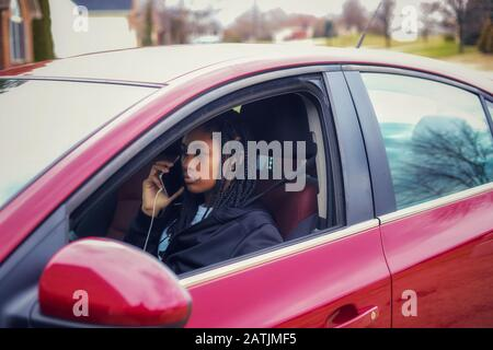 portrait of an African-American teenaged girl sitting in a car a talking on  her cellphone Stock Photo
