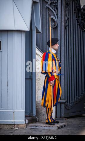 A Pontifical Swiss Guard stands outside an entrance to St. Peters Basilica, Vatican City, Rome, Italy. - Stock Photo