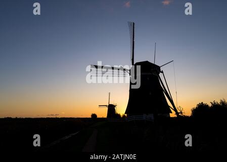 Windmills are silhouetted against the evening sky - Stock Photo