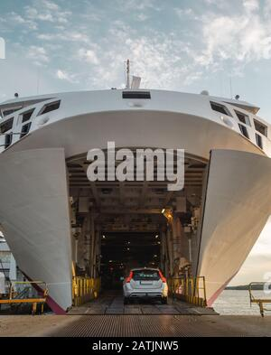 Bow doors are open and cars are driving inside a big car ferry in the port of Turku Finland in the evening - Stock Photo