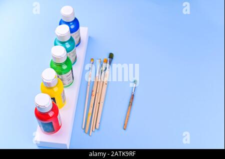 A set of acrylic paints in jars for the artist. Different color paints and brushes on a blue background. Flat lay. Copy space. - Stock Photo