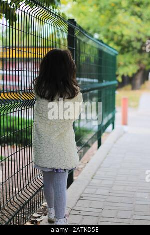 A little girl with long dark hair in a fluffy white coat turned away near the metal fence. Blurred back street background - Stock Photo