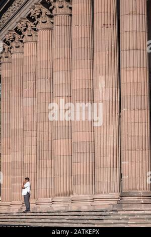A man stands by the massive pink quarry stone columns of the State Government Palace and Museum or Palacio de Gobierno del Estado de Nuevo Leon in the Macroplaza Grand Plaza alongside the Barrio Antiguo neighborhood of Monterrey, Nuevo Leon, Mexico. - Stock Photo