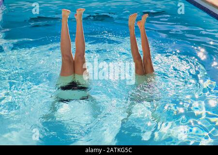 girls feet looking out of a swimming pool, the teenies are doing a handstand in the water - Stock Photo