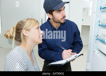 woman with engineer inspecting electric counter equipment - Stock Photo