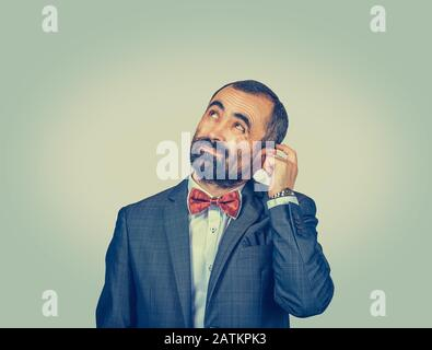 Closeup portrait man scratching head, thinking deeply about something, looking up, isolated on green-yellow wall background. Human facial expression, - Stock Photo