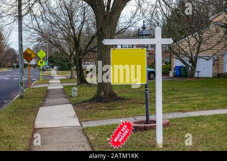 Blank yellow sign on a white post on a lawn in the front yard of a house near a sidewalk and a street - Stock Photo
