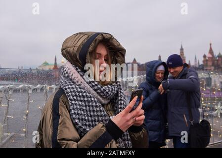 Tourists on the background of red square turned away from the panorama and look at their phones. - Stock Photo