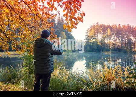A man stands on the picturesque lakeshore in the evening. The man takes a photo of the lake with a mobile phone - Stock Photo