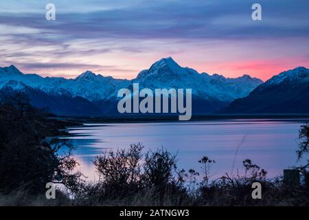 Beautiful colorful sunrise over glacial Lake Pukaki and Mount Cook from near Twizel, winter, New Zealand - Stock Photo